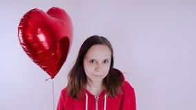 Девушка в красной фуфайке в ее руке красный воздушный шар в форме сердца Студент представляя на белой предпосылке стоковые изображения
