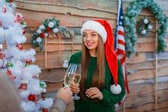 Девушка в красной шляпе держит стекло шампанского и приветственных восклицаний с парнем indoors стоковое изображение