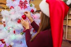 Девушка в красной шляпе Санты висит игрушку дерева на рождественской елке indoors стоковое изображение