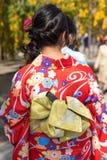 Девушка в красном кимоно на улице города, токио, Японии вертикально Конец-вверх задний взгляд Стоковые Фото