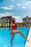 Девушка в красном купальном костюме около бассейна стоковое изображение