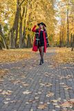 Девушка в красном пальто идет через лес парка осени Стоковые Фотографии RF