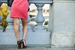 Девушка в красном платье на фоне перил стоковые изображения