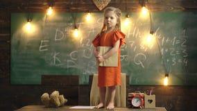 Девушка в красном платье с книгой в ее руках стоит на таблице в школьном классе E Помогать учителя сток-видео