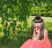 Девушка в красном платье есть яблоко Стоковые Изображения
