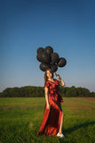 Девушка в красном платье при черные воздушные шары стоя в поле Стоковое Фото