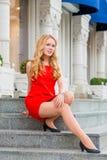 Девушка в красном платье сидя на шагах Стоковое Изображение