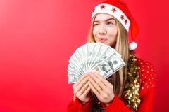 Девушка в красном свитере и шляпе Санта, держит деньги и взгляды прочь думая где потратить ее на красная предпосылка стоковое изображение rf