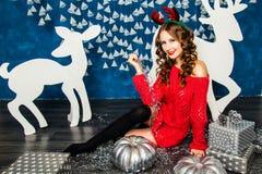 Девушка в красном свитере сидя с подарками рождества Жулик Нового Года Стоковые Изображения