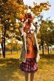 Девушка в красных скачках крышки с букетом осени листьев стоковая фотография