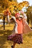 Девушка в красных скачках крышки с букетом осени листьев стоковая фотография rf