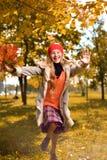 Девушка в красных скачках крышки с букетом осени листьев стоковые фотографии rf