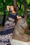 Девушка в красочном платье представляя с бронзовой скульптурой льва стоковые изображения rf