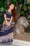 Девушка в красочном платье представляя с бронзовой скульптурой льва стоковое фото