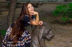 Девушка в красочном платье представляя с бронзовой скульптурой льва стоковые фото