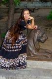 Девушка в красочном платье представляя с бронзовой скульптурой льва стоковая фотография