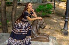 Девушка в красочном платье представляя с бронзовой скульптурой льва стоковые фотографии rf