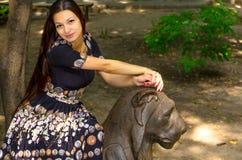 Девушка в красочном платье представляя с бронзовой скульптурой льва стоковая фотография rf
