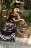 Девушка в красочном платье представляя с бронзовой скульптурой льва стоковые изображения