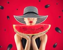 Девушка в купальнике с арбузом в руке и красной предпосылке с семенами стоковые изображения rf