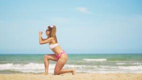 Девушка в купальном костюме играет спорт против фона моря Эффективные тренировки для батокс сток-видео
