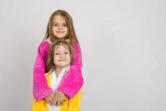 Девушка в купальном халате обнимая ее сестру купальный халат Стоковая Фотография