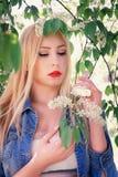 Девушка в куртке джинсовой ткани наслаждается цветками рано утром Стоковое Фото