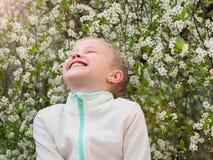 Девушка в куртке спорт смеется над весело в парке весны стоковая фотография rf
