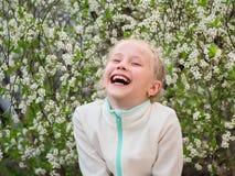 Девушка в куртке спорт смеется над весело в парке вишни весны стоковое фото rf