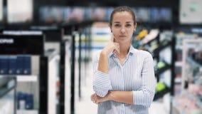 Девушка в магазине косметики думает, какой продукт купить, делает смешное лицо, медленное движение сток-видео