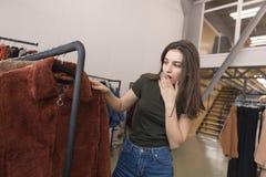 Девушка в магазине одежды выбирает новую меховую шыбу стоковая фотография rf