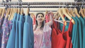 Девушка в магазине одежды выбирает платье сток-видео