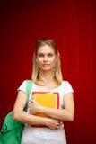 Девушка в наушниках и с тетрадями на пустой предпосылке стоковая фотография