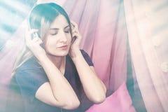 Девушка в наушниках слушая музыку и наслаждаясь усмехаться стоковые изображения