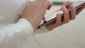 Девушка в наушниках учит в планшете на seashore и усмехаться Покупки женщины онлайн в онлайн магазине Конец-вверх акции видеоматериалы