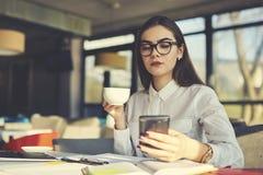 Девушка в обратных связях чтения деятельности стекел на вебсайте через smartphone во время перерыва на чашку кофе сидя в кафе Стоковые Изображения