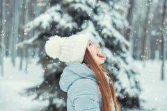 Девушка в одеждах зимы и шляпе улавливает снежинки с ее языком, радуется в снеге и зиме Стоковое фото RF