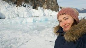 Девушка в одеждах зимы принимает selfie против скалистого берега острова Olkhon в Сибире Selfie на путешественнике телефона стоковая фотография