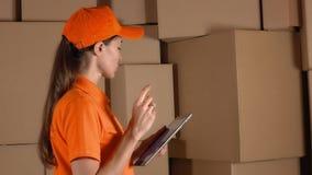Девушка в оранжевой форме подсчитывая ящики для хранения и используя ее таблетку против коричневого цвета cartons backround дело  видеоматериал