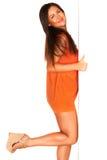 Девушка в оранжевом платье за белой стеной Стоковое Изображение