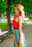 Девушка в оранжевом платье представляя в парке Стоковые Изображения RF