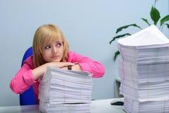 Девушка в офисе безвыходно смотря стог документов стоковые фото