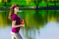 Девушка в одеждах спорта держит бутылку воды, смотрящ отсутствующей и усмехаться, стоя на пляже после разминки Стоковая Фотография