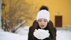 Девушка в пальто норки дует снег от ее mittens сток-видео