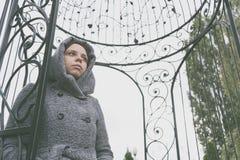 Девушка в пальто представляя снаружи в осени в хмурой погоде, всматриваясь заботливо в расстояние концепция depre осени стоковая фотография