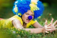 Девушка в парике клоуна с голубым носом лежит на зеленой траве Стоковая Фотография RF