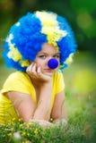Девушка в парике клоуна с голубым носом лежит на зеленой траве Стоковые Изображения