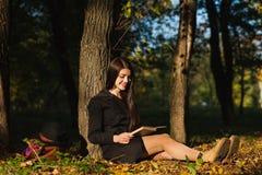 Девушка в парке прочитала книгу Стоковое фото RF