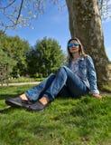 Девушка в парке сидит на том основании деревом Стоковая Фотография RF