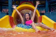 Девушка в парке aqua имеет потеху ехать на водных горках с раздувным кольцом стоковые фото